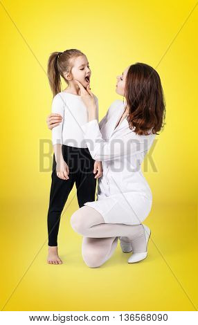 Doctor examining throat of little girl on the yellow background