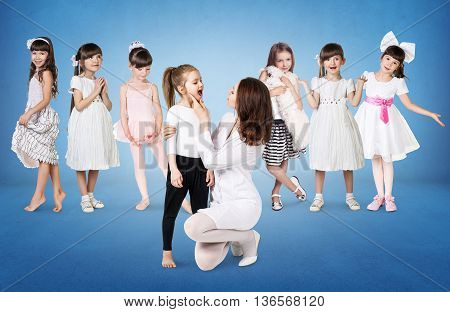 Doctor examining throat of little girl on the many girls backgound