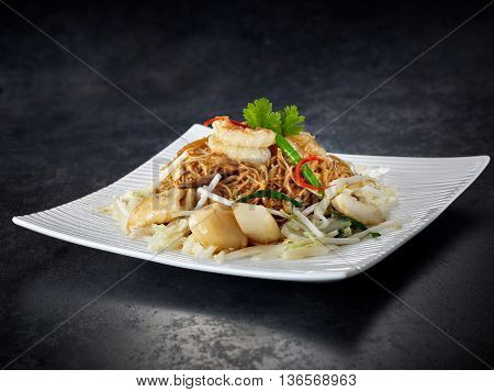 Seafood spaghetti with scallops and shrimps on white plate