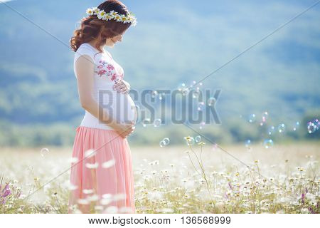 Beautiful pregnant woman with long curly brown hair, dressed in a white T-shirt without sleeves, on his head wearing a wreath of white daisies, spends a summer day in a field of blossoming daisies, blowing bubbles