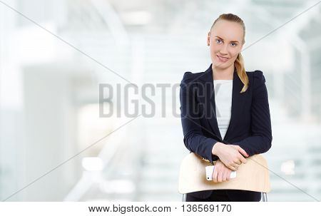 Beautiful woman in business style standing on the blurred background of the stairs