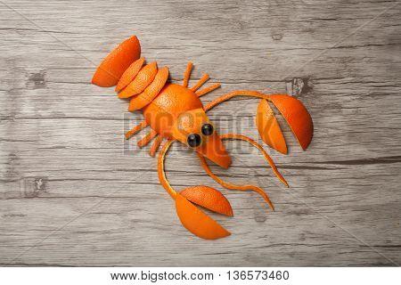 Crayfish made of orange on wooden background
