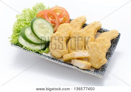 Chicken Nuggets with sliced cucumber and tomato on plate