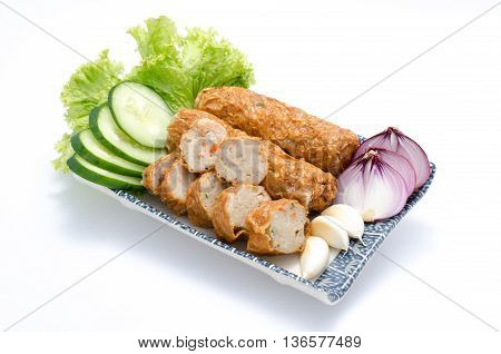 Ngor Hiang or fish paste with garlic onion sliced cucumber and salad on plate