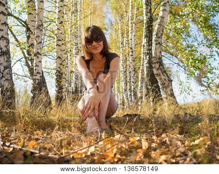 smiling woman looking at the camera on a background of autumn forest