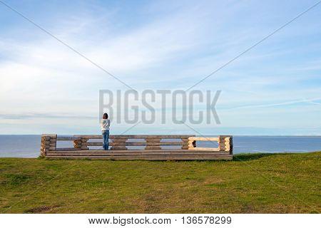 woman looking at the lake and sky