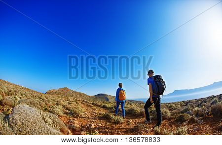 couple of travelers with backpack walking on the trail against sea and blue sky at early morning. Balos beach on background, Crete, Greece