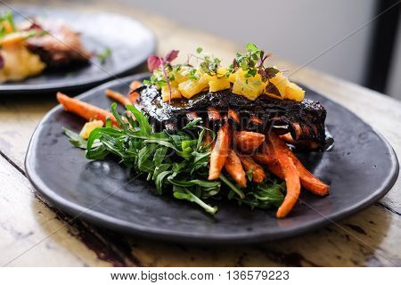 Roasted pork ribs with potato and herbs on black plate