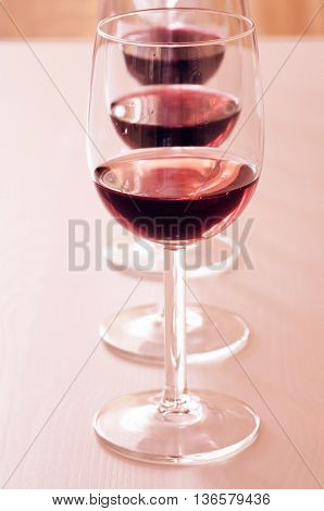 Three glasses with different red wines in line