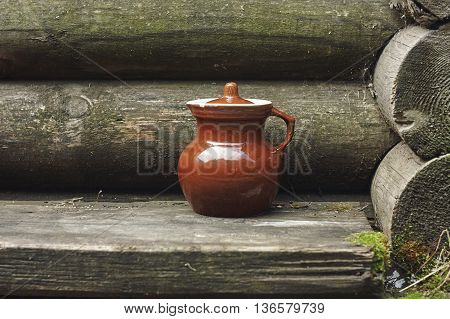 brown old jug near blockhouse wall close up