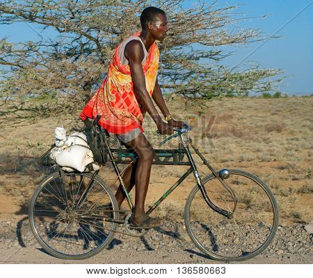 NORTHERN KENYA-JAN 05: Turkana man in traditional clothes rides a bicycle Jan 5 2013. The Turkana people are the second largest of the pastoral people of Kenya. They occupy an area of about 67000 square kilometers.