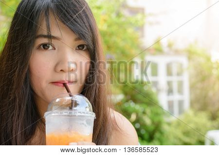 Drinks people and lifestyle concept - close up of woman drinking ice tea from plastic cup with straw at cafe