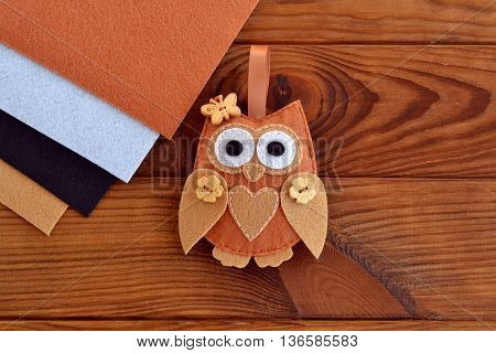 Home decor cute toy on wooden background. Felt owl sewing pattern. Soft owl embellishment or ornament. Brown, white, beige and black felt sheets. Crafts sewing project for kids