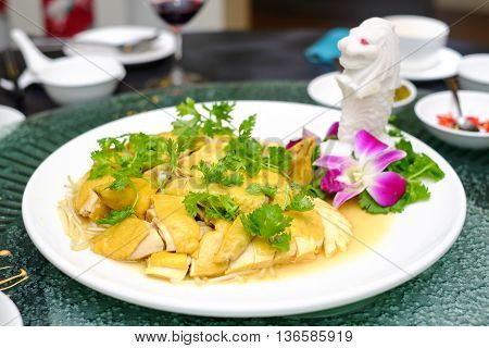 Chopped steamed chicken in Singapore style on white plate in restaurant