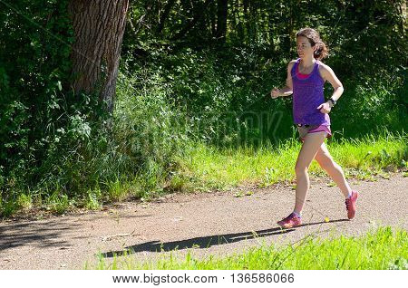 Active woman runner jogging in park, outdoors running, sport and healthy lifestyle concept