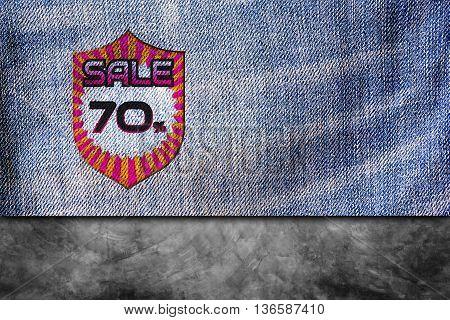 Sale discount labels. 70% off on blue denim jeans background.