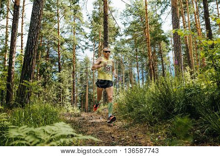 Miass Russia - June 26 2016: athlete leader of race runs along trail in woods during Marathon