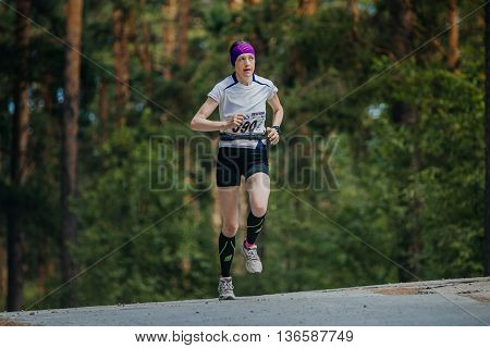 Miass Russia - June 26 2016: female athlete running on road in forest during Marathon