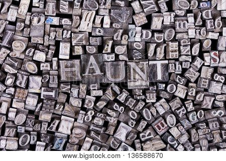 Close Up Of Typeset Letters With The Word Haunt