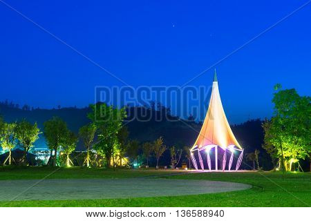 small outdoor tent with sharp top in garden at night on view from grassland