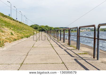 Old concrete embankment at river background in city