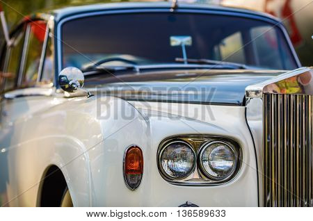 MINSK BELARUS - MAY 07 2016: Close-up photo of Rolls Royce. Close-up of vintage luxury car. Selective focus on headlight.