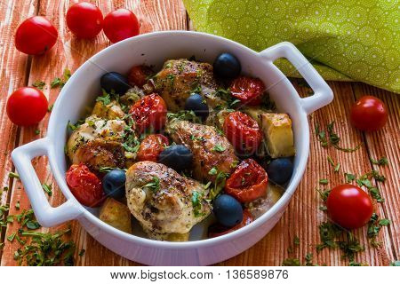 Chicken legs with potatoes cherry tomatoes and black olives. White baking dish on wooden background.