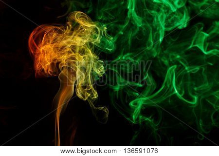 Abstract art. Color yellow green smoke from the aromatic sticks on a black background. Background for Halloween. Texture fog. Design element. The concept of aromatherapy.