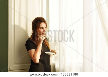 Pretty girl drinking morning coffee near window. Good morning