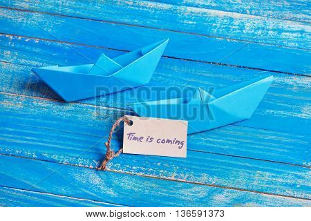 Label with the Words Time is coming. Paper Boat with a sign
