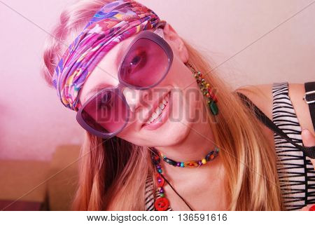 Hippie girl in sunglasses looks into the camera her head tilted. Toned image pink filter
