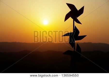 Peaceful and serene image of still pinwheel outlines against a sunset horizon.