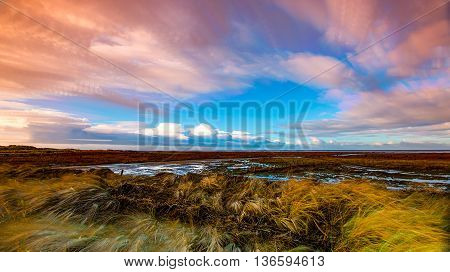 timelapse movement of clouds across marshland and grasses