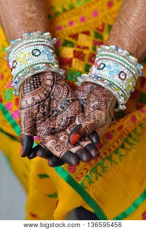 Indian bride's hand with henna tattoo design and traditional bangles