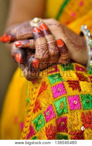 Indian woman's hand with henna tattoo and traditional Indian sari