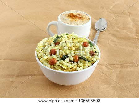 Spicy puffed rice, a popular and traditional Indian snack, in a bowl, and coffee.