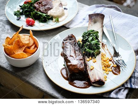 Roasted mutton ribs with fried potato and salad on table