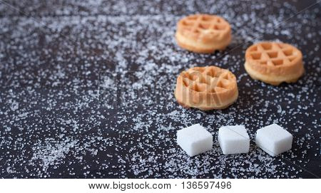 Three delicious waffles and three pieces of sugar on a dark background