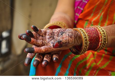Close up photo of Indian woman's palms with henna tattoo and red bangles