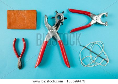Working tools for embossed leather on blue background top view