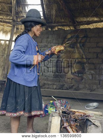 October 22 2012 - Paru Paru, Peru: Native Peruvian woman preparing guinea pigs over fire. Guinea pigs are special dish in Peru prepared for weddings and religious ceremonies.