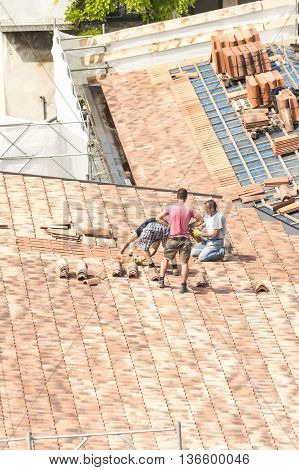 Udine , Italy - May 26 , 2016 : Construction site. Masons to work on the roof for laying tile