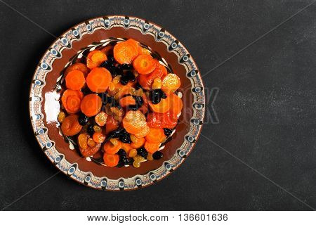 Traditional Jewish Tzimmes dish prepared with carrot and dried fruits on the black chalkboard