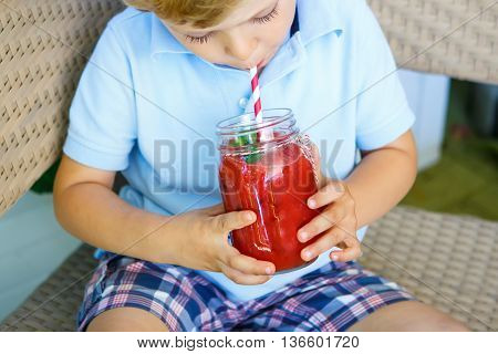 Adorable little kid boy drinking healthy fruits and vegetables juice smoothie in summer. Happy child enjoying organic drnk.
