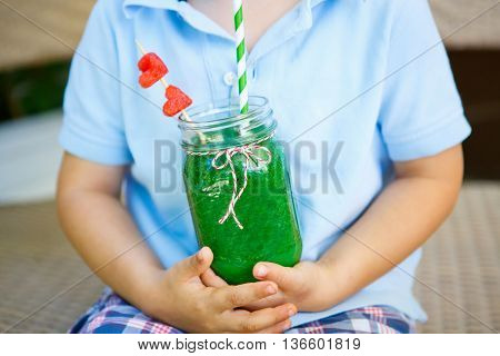 Adorable little kid  drinking healthy fruits and vegetables green juice smoothie in summer. Hands of child with drink.