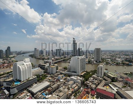 Cityscape and modern building near the river in the afternoon at Chao Phraya River in Bangkok Thailand under blue sky and cloud