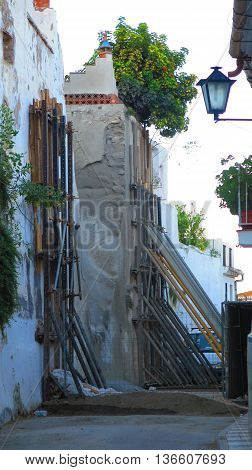 propping up retaining wall in narrow street in Alora Andalusia