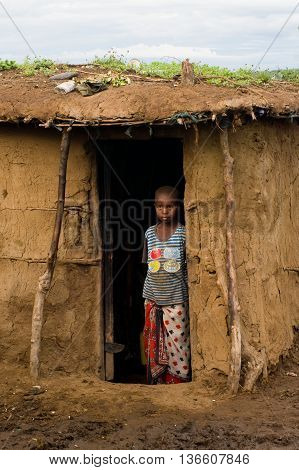 Maasai Child Near Traditional Hut