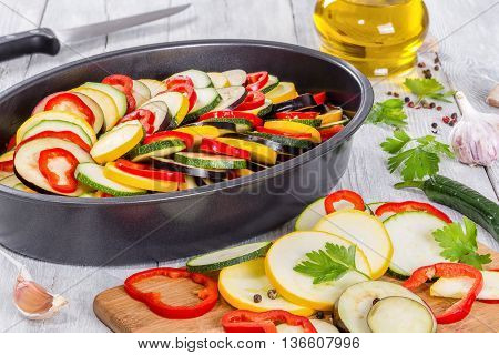 Raw ingredients for traditional French casserole ratatouille: zucchini red bell pepper yellow squash eggplant in a baking dish and on cutting board view from above