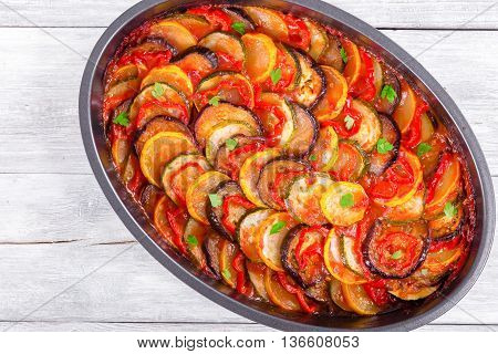 Layered ratatouille in a baking dish: slices of zucchini red bell pepper chili yellow squash eggplant olive oil parsley and garlic. white background top view